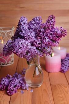 木製の表面のテーブルの上に花瓶の美しいライラックの花