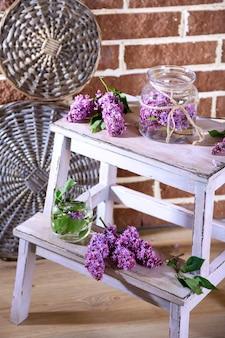 花瓶、木製のはしご、色の壁の背景に美しいライラックの花