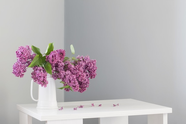 흰색 나무 테이블에 흰색 주전자에 아름 다운 라일락 꽃