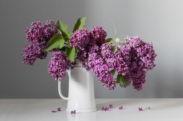Красивые сиреневые цветы в белом кувшине на белом деревянном столе