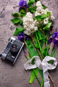 Beautiful lilac flowers and old camera on gray concrete background.