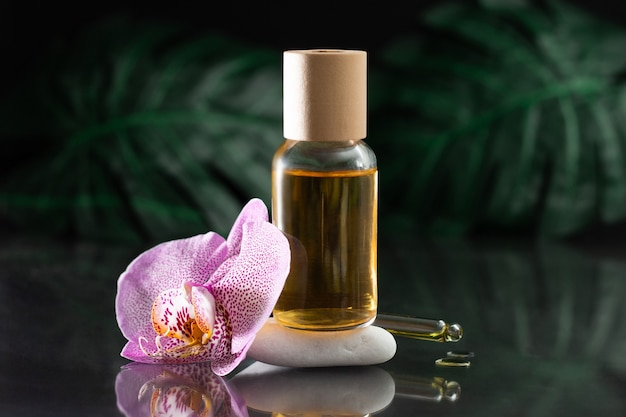Красивый сиреневый цветок орхидеи и прозрачная стеклянная бутылка желтого масла, стоящая на белом камне с капельницей или пипеткой и каплями масла, с листьями монстеры на черной отражающей поверхности