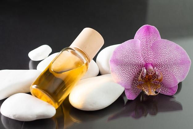 Красивый сиреневый цветок орхидеи и прозрачная стеклянная бутылка желтого масла или духов, лежащих на белых камнях на черной отражающей поверхности