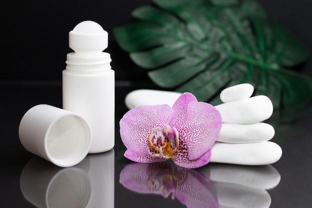 Красивый сиреневый цветок орхидеи и белый шариковый дезодорант с белыми камнями и листьями монстеры