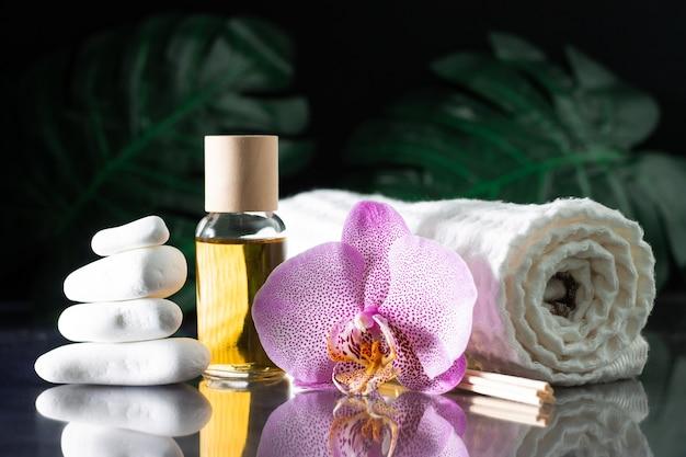 Красивый сиреневый цветок орхидеи, прозрачный флакон желтого масла или духов, деревянные палочки и свернутое полотенце со стопкой белых камней и листом монстеры