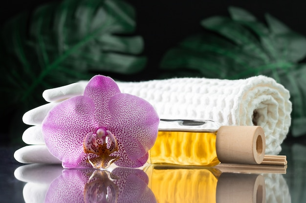 Красивый сиреневый цветок орхидеи, прозрачный флакон желтого масла или духов, деревянные палочки и свернутое полотенце
