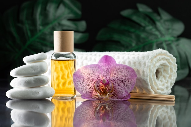 Beautiful lilac orchid flower, clear bottle of yellow oil or perfume, wooden sticks and rolled towel with stack of white stones and monstera leaves