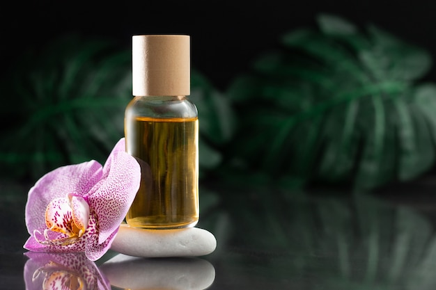 Beautiful lilac orchid flower and clear glass bottle of yellow oil or perfume standing on white stone with monstera leaves on black reflective surface