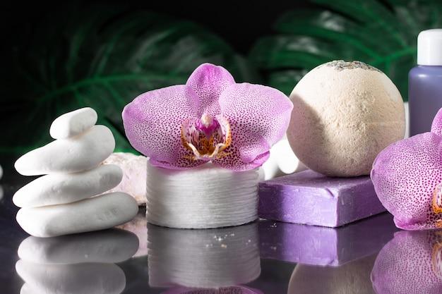 아름다운 라일락 난초 꽃, 화장품 병, 면화 패드 및 흰 돌과 몬스 테라 잎의 스택과 함께 수제 비누