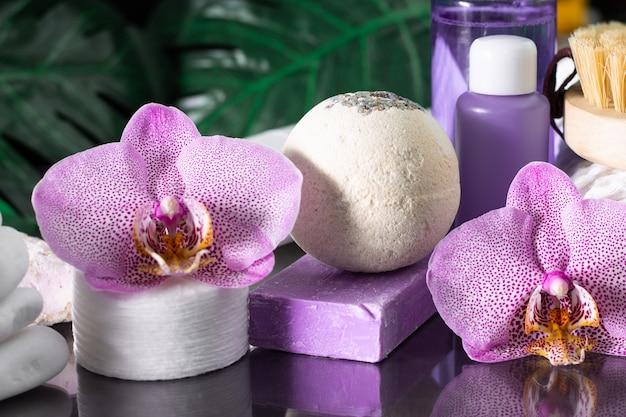 아름다운 라일락 난초 꽃, 화장품 병, 면화 패드 및 흰색 돌과 몬스 테라 잎의 스택과 함께 수제 비누