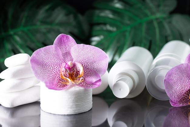 아름 다운 라일락 난초 꽃, 흰색 화장품 병, 흰색 돌과 몬스 테라의 스택과 함께 목화 패드 검은 표면에 나뭇잎.
