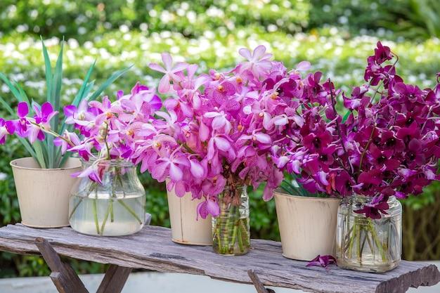 열대 정원의 꽃병에 있는 아름다운 라일락 분홍색 난초, 가까이, 야외, 자연 개념. 나무 테이블, 아시아, 태국에 이국적인 다채로운 난초 꽃다발