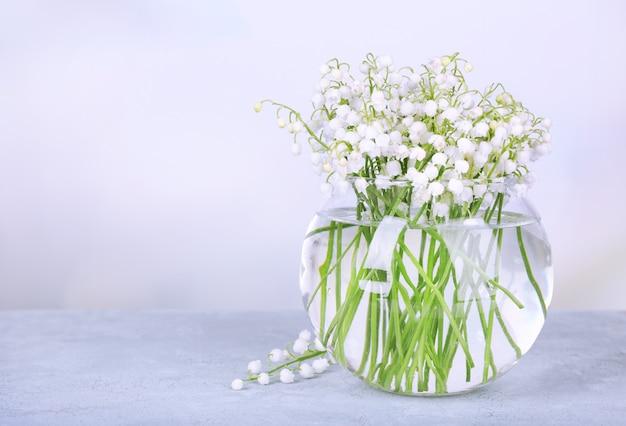 밝은 배경에 유리 꽃병에 계곡의 아름다운 백합