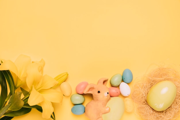 Beautiful lily flowers with easter eggs and nest on yellow backdrop