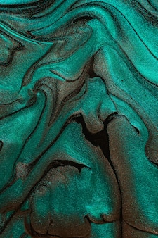 Beautiful liquid texture of the nail polishorangeyellow and green colorsfluid art background