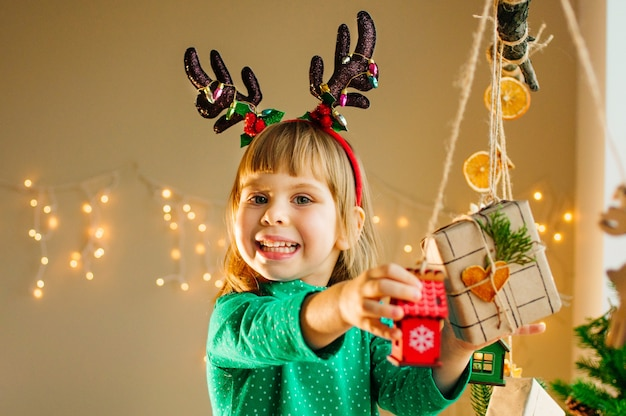 Красивая маленькая 3-летняя девочка держит подарочную коробку, украшенную сушеными цитрусовыми ломтиками в форме сердца. выборочный фокус. Premium Фотографии