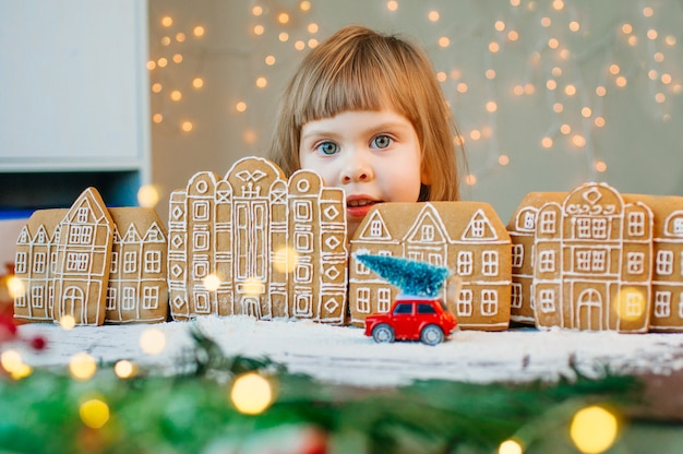 Красивая маленькая 3-летняя девочка играет с игрушкой автомобиля с елкой в городке пряников. селективный акцент на девушке.