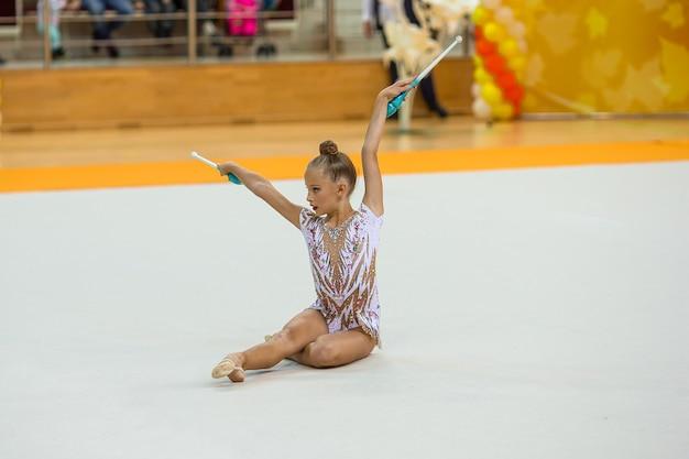 Красивая маленькая активная гимнастка со своим выступлением на ковре