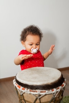 Beautiful little african kid playing drum