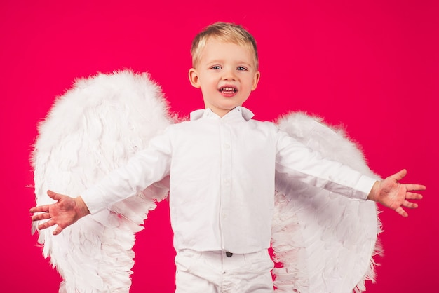 Beautiful little angel boy small cupid isolated on a red background cute little boy with white wings