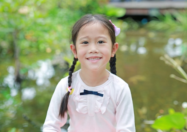 Beautiful little asian child girl in the nature garden.