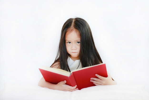 Beautiful little asian child girl reading hardcover book lying with pillow on white background.
