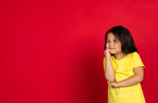 Красивая маленькая азиатская девушка жесты изолирована на красном