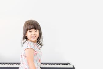 Красивая маленькая азиатская девушка играет на фортепиано в гостиной.