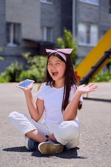 Красивая маленькая азиатская девушка с телефоном на улице удивлена