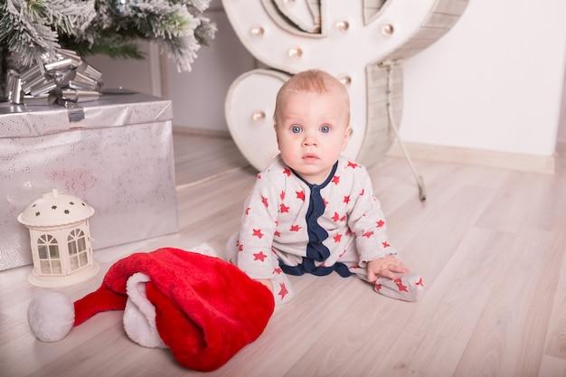 Красивый маленький ребенок празднует рождество. новогодние каникулы. малышка в новогоднем костюме с подарком