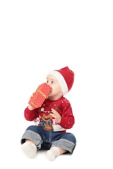 美しい小さな赤ちゃんは、分離されたギフトでクリスマスを祝います
