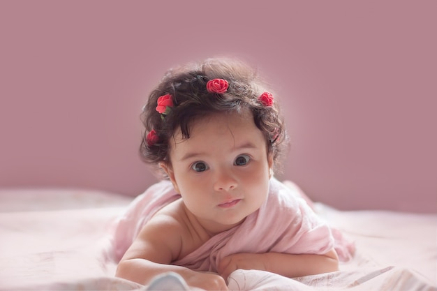 Beautiful little baby girl on a pink background