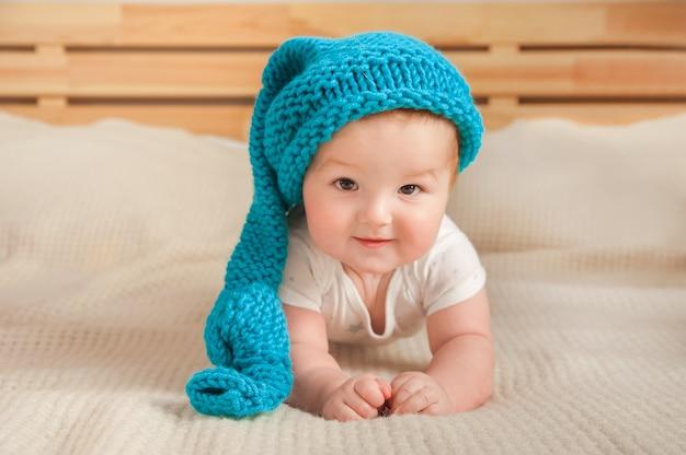 침대 클로즈업에 모자에 아름 다운 작은 아기. 큰 파란색 재미있는 모자에 나가서는 아기.