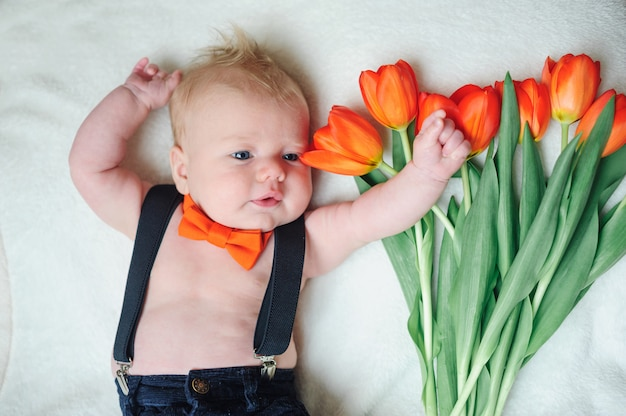 Beautiful little baby lying near tulips