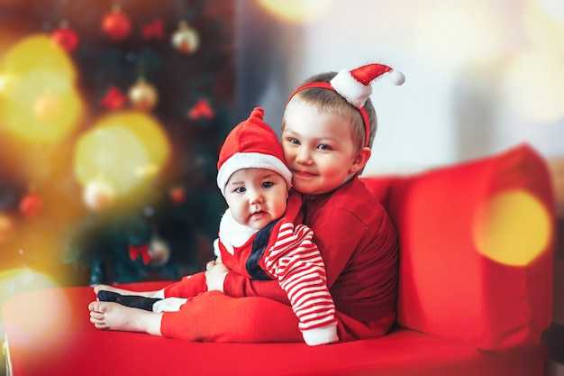 Beautiful little baies celebrate christmas. new year's holidays. babies in a christmas costume