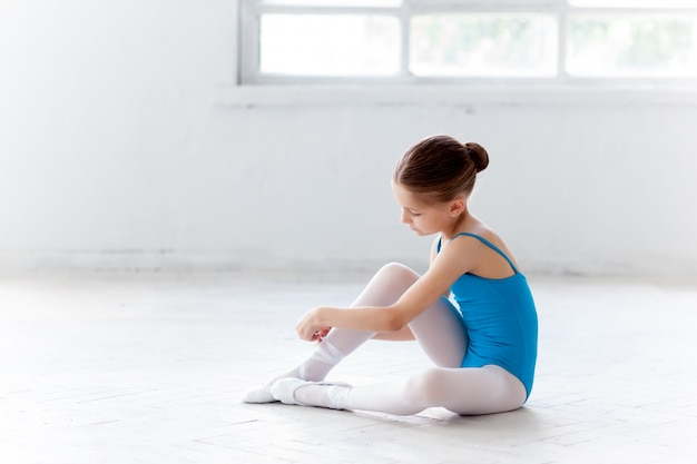 Bellissima piccola ballerina in abito blu per ballare mettendo a piedi scarpe da punta