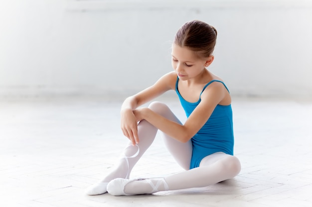Beautiful little ballerina in blue dress putting on foot pointe shoes