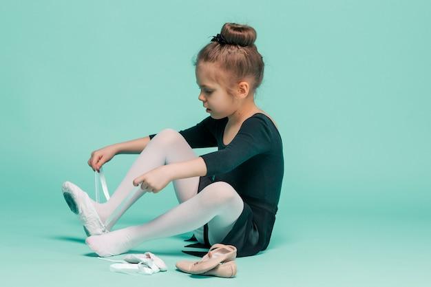 Красивая маленькая балерина в черном платье для танцев надевает пуанты