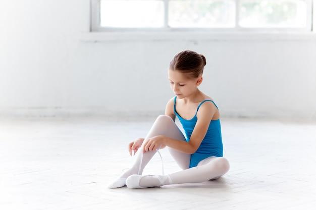 발 포인트 신발을 신고 춤을 추기 위해 파란색 드레스를 입은 아름다운 작은 발레리나