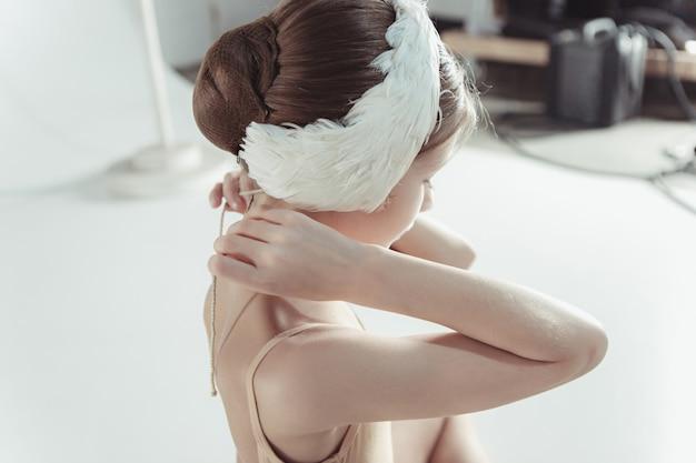 그녀의 머리에 하얀 백조 붕대를 입고 아름다운 작은 발레리나