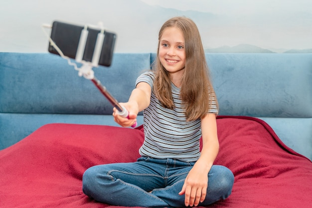 Beautiful little blogger girl recording a video blog at home with a selfie stick
