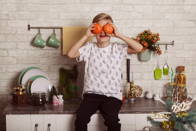 A beautiful little blond boy sits on the kitchen table and closes his eyes with oranges. funny photo