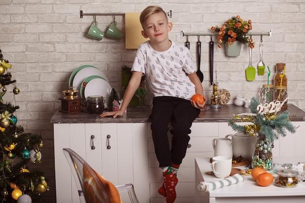 美しい小さな金髪の少年は台所のテーブルに座って、彼の手でオレンジを保持