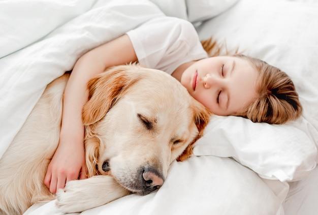 골든 리트리버 강아지와 함께 침대에 머물고 있는 아름다운 금발 머리 소녀