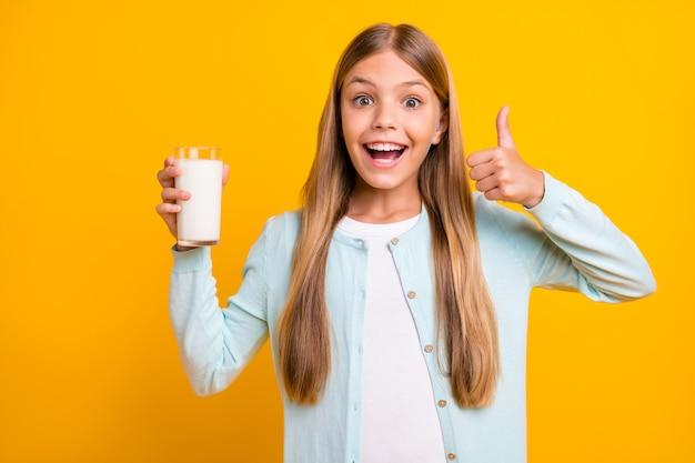 美しい小さなブロンドの女性は、ミルクをアドバイスする腕を上げる親指を保持します
