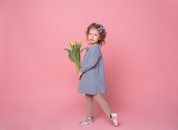 Beautiful little blonde girl in blu dress with bouquet of yellow tulips on pink background with space for text.