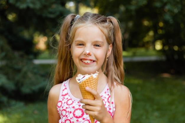 Красивая маленькая белокурая девочка ест мороженое летом в парке. веселая девушка с мороженым.
