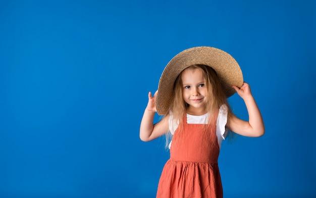 텍스트에 대 한 공간을 가진 파란색 표면에 밀 짚 모자에 아름 다운 작은 금발 소녀