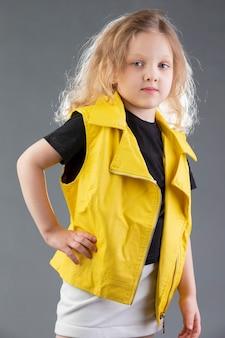 회색 배경에 노란색 재킷을 입은 아름다운 금발 소녀. 다섯 살 소녀입니다. 어린이를 위한 모델 테스트.