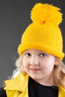 Красивая маленькая блондинка в желтой вязаной шапке на сером фоне.
